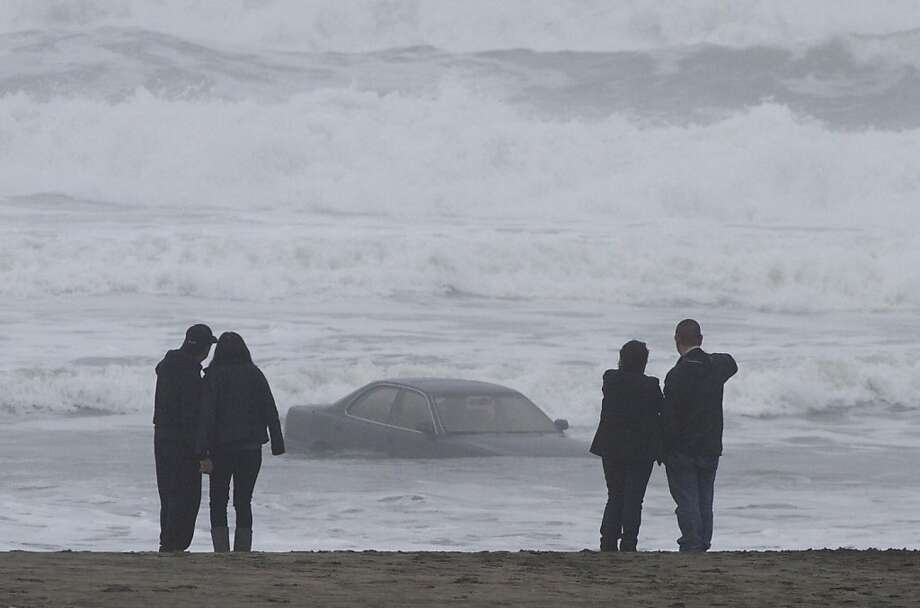 People view a Lexus car stuck in the waves along San Francisco's Ocean Beach on Friday morning, Feb. 10, 2012. A woman suffered minor injuries this morning when she drove her car into the water at San Francisco's Ocean Beach, a fire dispatcher said. Photo: Douglas Zimmerman, SF Gate