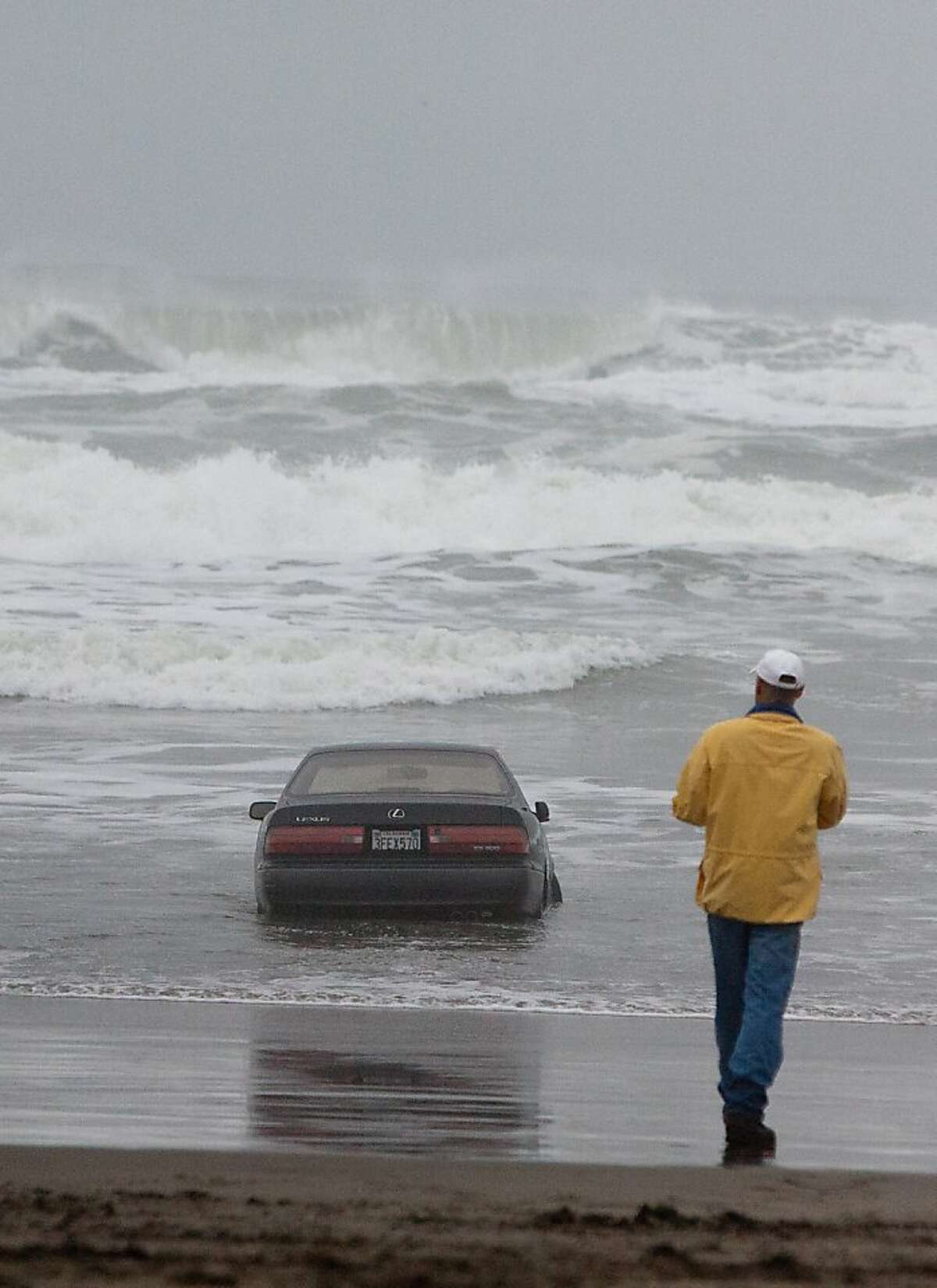People view a Lexus car stuck in the waves along San Francisco's Ocean Beach on Friday morning, Feb. 10, 2012. A woman suffered minor injuries this morning when she drove her car into the water at San Francisco's Ocean Beach, a fire dispatcher said.