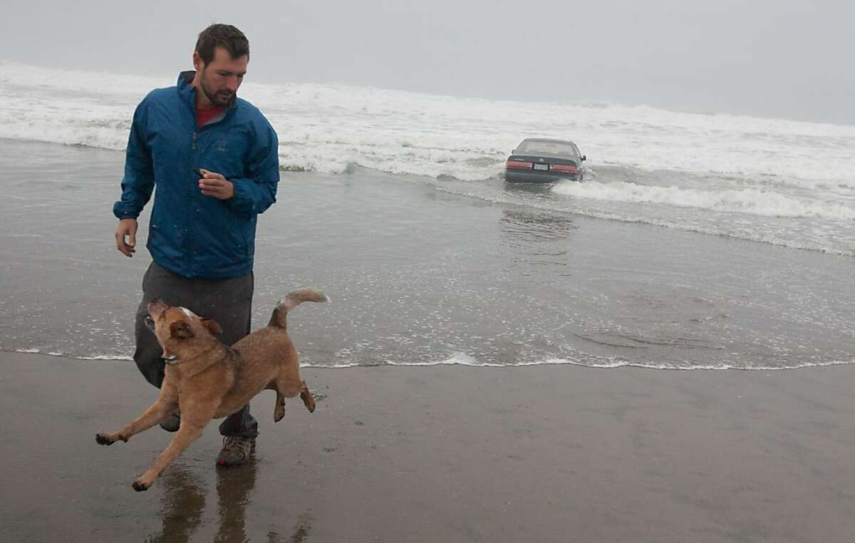 Alex Becker of the Richmond District of San Francisco and his dog Marv run away from an oncoming wave after Becker took a photo of a Lexus car stuck in the waves along San Francisco's Ocean Beach on Friday morning, Feb. 10, 2012. A woman suffered minor injuries this morning when she drove her car into the water a fire dispatcher said.