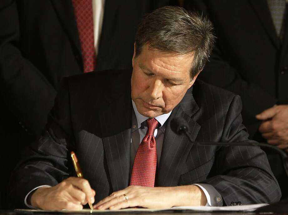 Ohio Gov. John Kasich signs Senate Bill 5 into law Thursday, March 31, 2011, in Columbus, Ohio. Ohio's governor on Thursday signed into law a limit on the collective bargaining rights of 350,000 public workers, defying Democrats and other opponents of themeasure who have promised to push for repeal. Photo: Jay LaPrete, AP