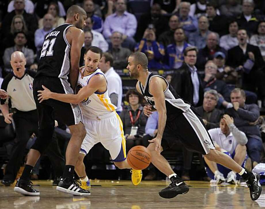 Stephen Curry is screened out by Tim Duncan as Tony Parker drives the lane in the fourth quarter at Oracle Arena in Oakland on Monday. Photo: Carlos Avila Gonzalez, The Chronicle