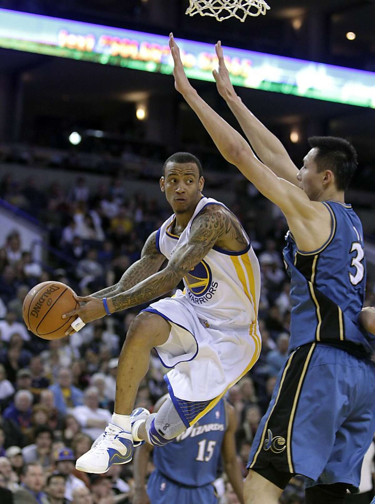 Golden State Warriors' Monta Ellis, left, looks to pass away from Washington Wizards' Yi Jianlian, of China, during the first half of an NBA basketball game, Sunday, March 27, 2011, in Oakland, Calif.