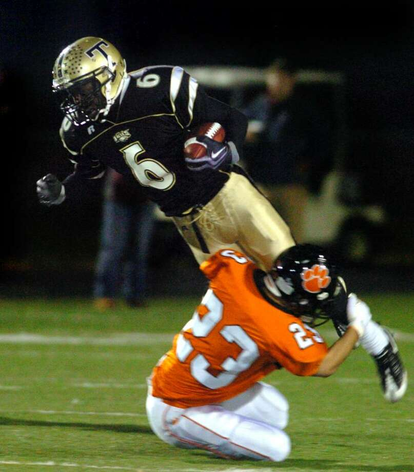 Trumbull's Frank Gaines is tripped up by Ridgefield's Casey McKnight during the second half of Friday night's game at McDougall Field in Trumbull. Photo: Autumn Driscoll / Connecticut Post