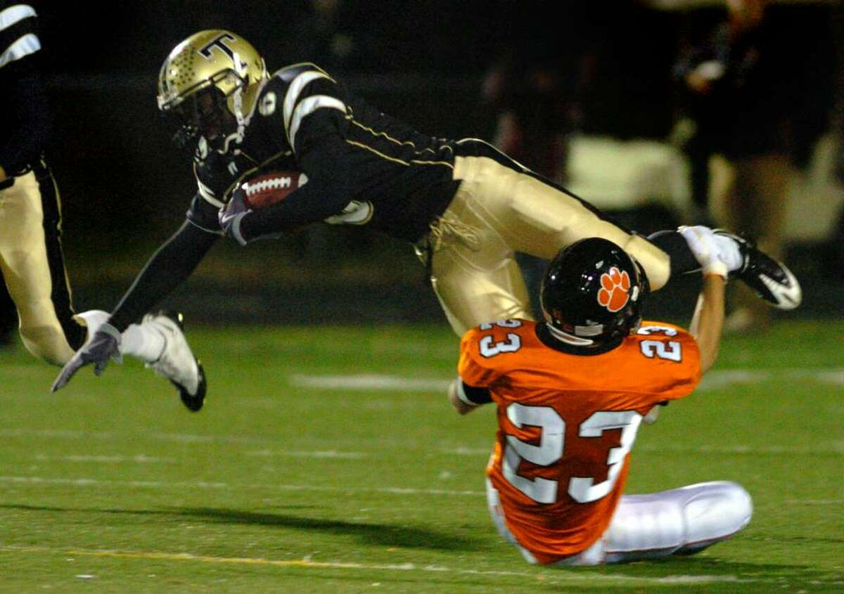 Trumbull's Frank Gaines is tripped up by Ridgefield's Casey McKnight during the second half of Friday night's game at McDougall Field in Trumbull.