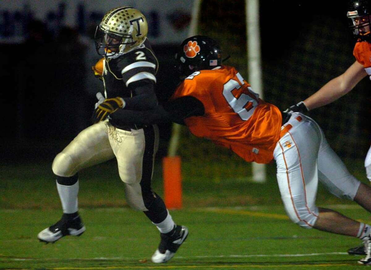 Trumbull's Will Melvin is brought down by Ridgefield's Dan Sheldon during the second half of Friday night's game at McDougall Field in Trumbull.