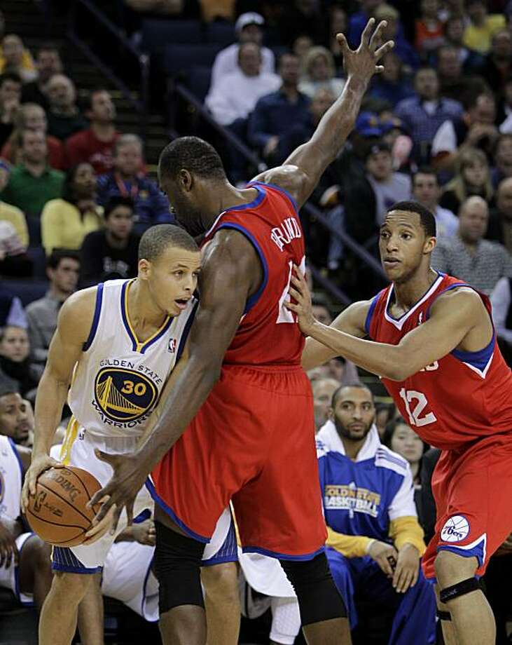 Golden State Warriors' Stephen Curry, left, looks for a way around Philadelphia 76ers' Elton Brand (42) and Evan Turner (12) during the first half of an NBA basketball game Monday, Dec. 27, 2010, in Oakland, Calif. Photo: Ben Margot, AP