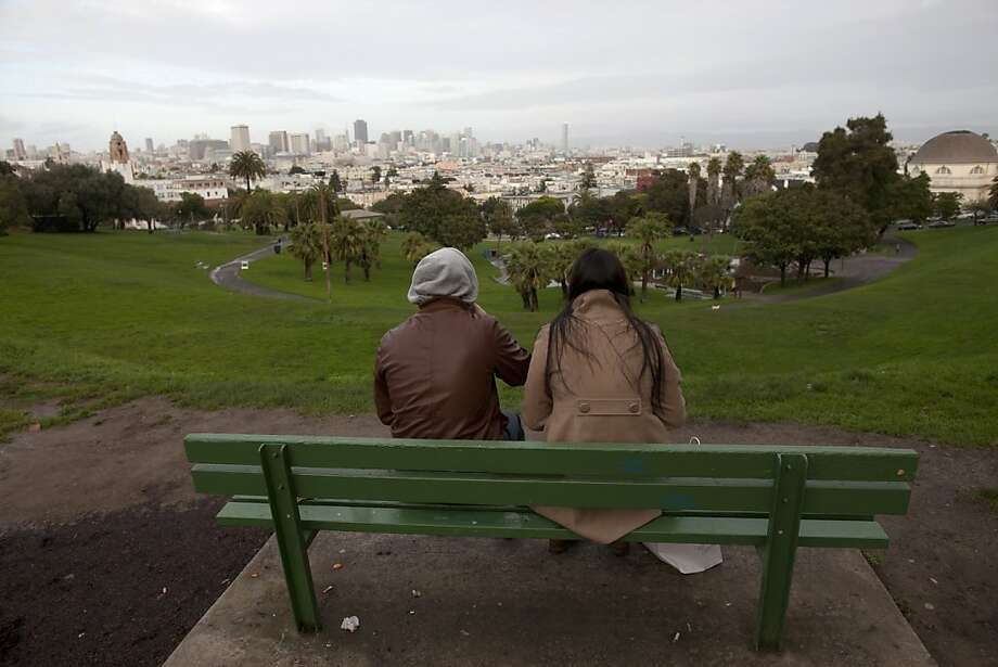 Two peoplel enjoy the view frorm the top of Delores Park in the Mission District on December 19, 2010 in San Francisco, Calif.  Photograph by David Paul Morris/Special to the Chronicle Photo: David Paul Morris, Special To The Chronicle