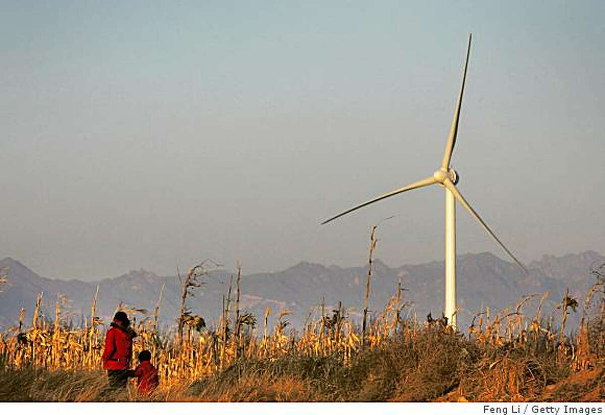 """BEIJING - DECEMBER 13: A mother and child walk past a wind turbine on the south bank of Guanting Reservoir on December 13, 2007 in Beijing, China. Beijing has put forward """"Green Olympics"""" as one of the three themes for the 2008 Olympic Games. Guanting Wind Power Field will begin operation at the end of this month with 33 wind turbines producing 50,000 kw, according to local media. China has accelerated its development of wind resources and other clean energy to meet its vast long-term energy needs, and help to achieve the """"Green Olympic"""" goal. (Photo by Feng Li/Getty Images)"""