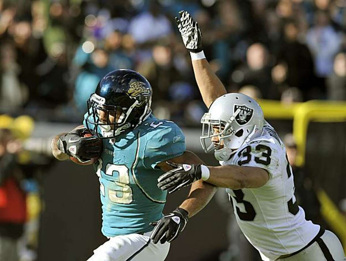 Jacksonville Jaguars running back Rashad Jennings (23) out runs Oakland Raiders safety Tyvon Branch (33) to score a touchdown during the second half of an NFL football game in Jacksonville, Fla., Sunday, Dec. 12, 2010. Jacksonville Jaguars beat the Oakland Raiders 38-31.