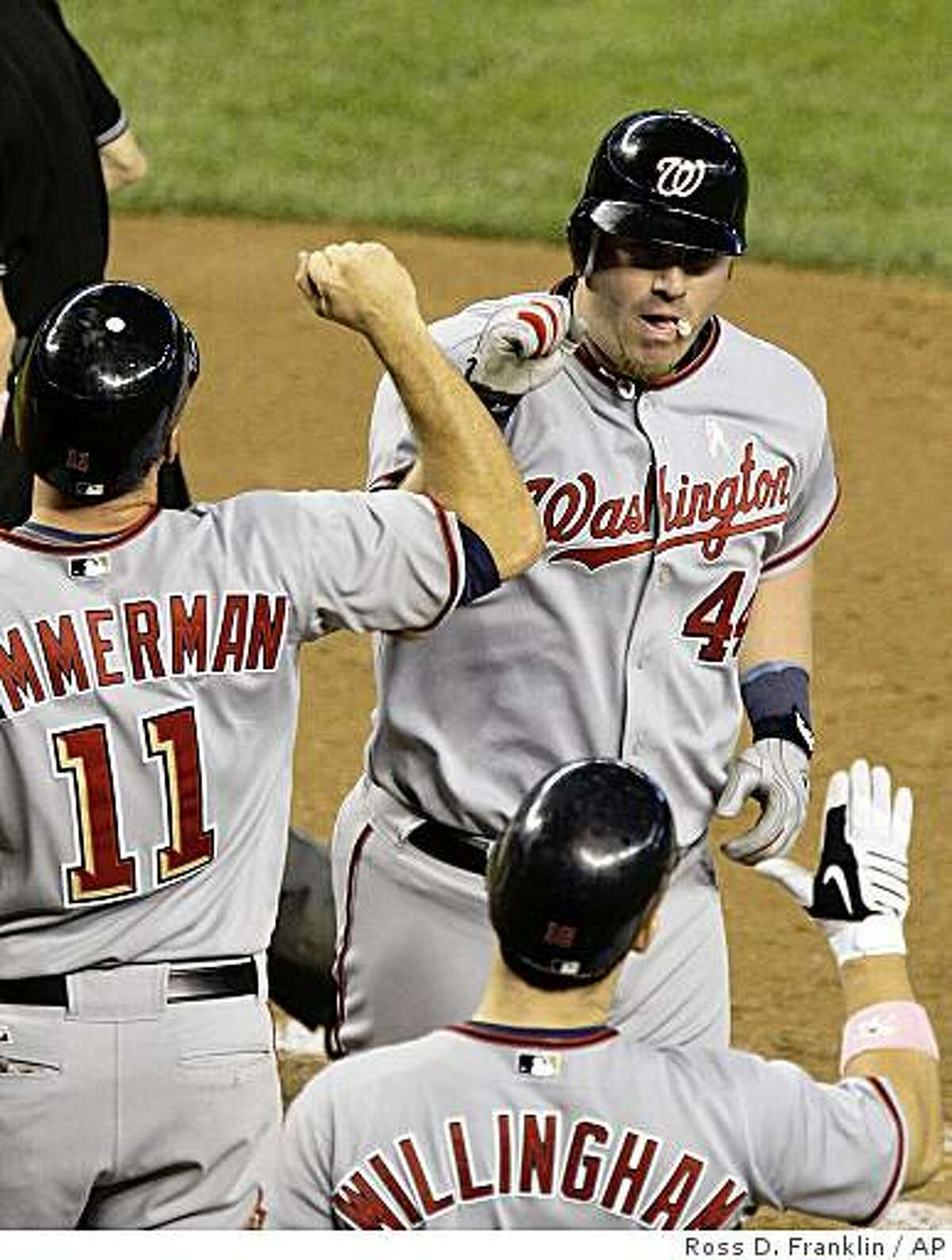 Washington Nationals' Adam Dunn, top right, celebrates his second home run of the game against the Arizona Diamondbacks with teammates Ryan Zimmerman (11), and Josh Willingham in the fifth inning during a baseball game Sunday, May 10, 2009, in Phoenix. (AP Photo/Ross D. Franklin)