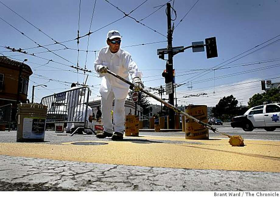 Pat O'Gorman with the Dept of Public Works, spread yellow paint in the intersection which will be closed to traffic soon. A small stretch of 17th Street near Castro will be turned into a trial pedestrian plaza, and a no-car zone. Photo: Brant Ward, The Chronicle