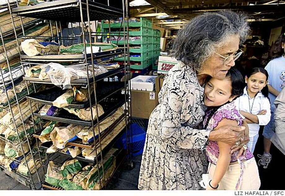 Mother Mary Ann Wright's warehouse where she distributes food and clothing to thise in need. Mother Wright hugs Mariah Sanchez, 10 years old. Her sister Marissa Sanchez (right), 7 years old, are both from Hayward. They are part of a homeschool group from San Leandro called East Hills 4H, and came by to do community service. The leftover bread of the day was driven to the poor at People's Park in Berkeley. Shot on 11/18/03 in San Francisco. Photo: LIZ HAFALIA, SFC