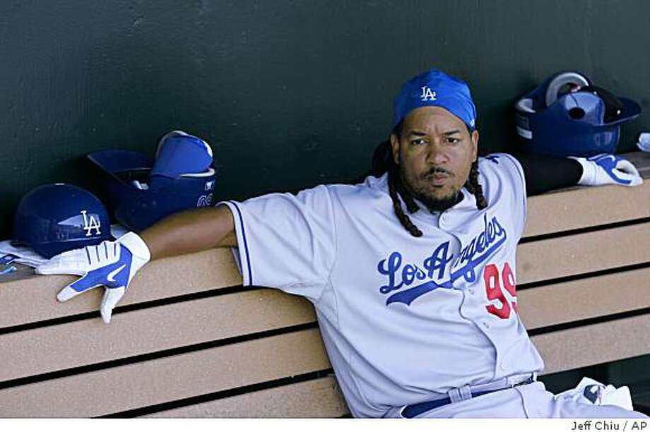 FILE - In this March 23, 2009 file photo, Los Angeles Dodgers' Manny Ramirez sits in the dugout against the Los Angeles Angels in a spring training baseball game in Tempe, Ariz. Ramirez has been suspended for 50 games by Major League Baseball, becoming by far the highest-profile player ensnared in the sport's drug scandals. (AP Photo/Jeff Chiu, File) Photo: Jeff Chiu, AP