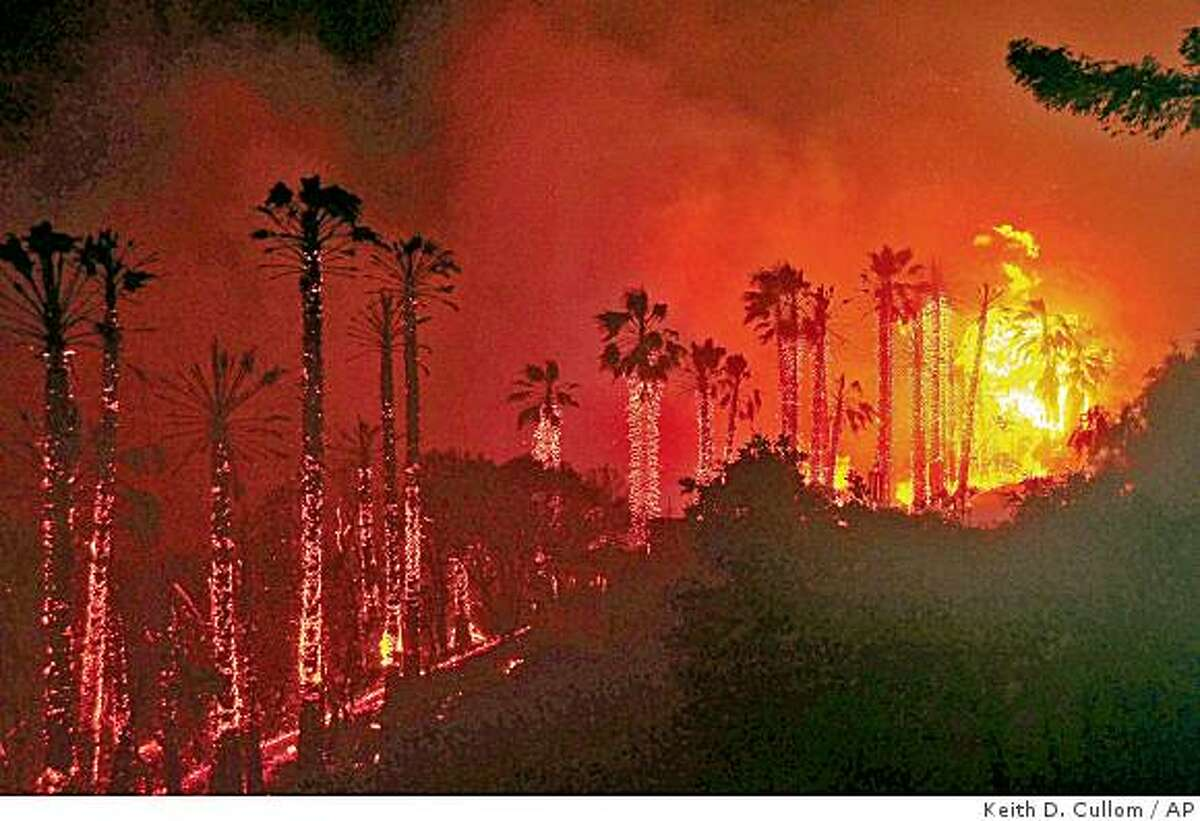 Towering Palm Trees explode as flames jump across state highway 154 early Friday morning May 8, 2009, in Santa Barbara, Calif., bringing the fire dangerously close to heavily populated areas.