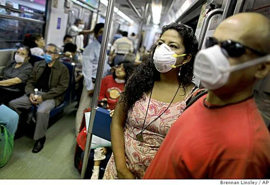 Passengers wearing masks as a precaution against the swine flu ride a subway train in Mexico City, Wednesday, May 6, 2009.  Mexico has ended a government-ordered shutdown designed to contain the swine flu virus outbreak. (AP Photo/Brennan Linsley) Photo: Brennan Linsley, AP