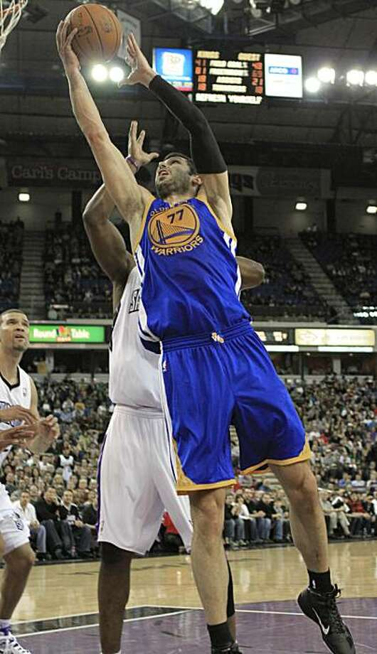 Golden State Warriors forward Vladimir Radmanovic, of Serbia, left, goes to the basket against Sacramento Kings forward Carl Landry, background as Kings forward Francisco Garcia, left, looks on late in the fourth quarter of an NBA basketball game in Sacramento, Calif., Tuesday, Dec. 21, 2010.  Radmanovic scored a three-point shot at the buzzer to tie the game and send it into overtime where the Warriors beat the Kings  117-109. Photo: Rich Pedroncelli, AP