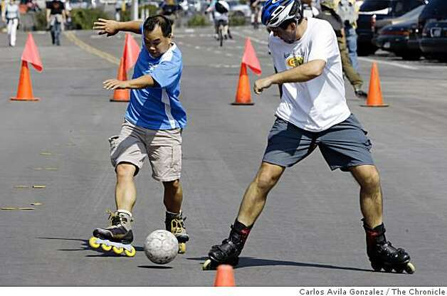 Raymond Chui, left, and Tom Blooming, right, play roller soccer on Terry A. Francois Street on Sunday, September 14, 2008, in San Francisco, Ca., during the city's Sunday Streets event.  Sunday is the second and last time this year the city experiments with closing down parts of San Francisco to encourage people to get out and about. The city has partnered with more than 100 sponsors and dozens of free activities will be offered along the route. Photo: Carlos Avila Gonzalez, The Chronicle
