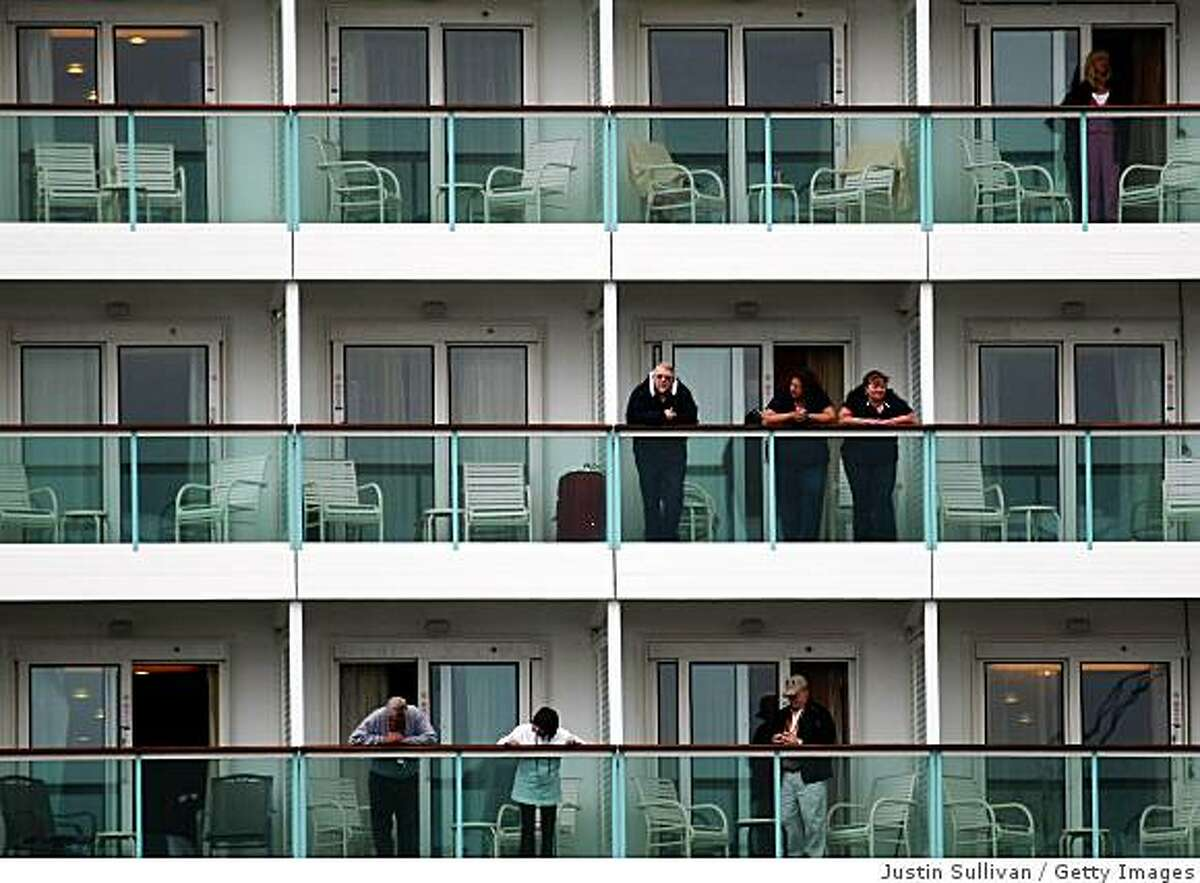 Cruise passengers look from their balconies after arriving in port in San Francisco.