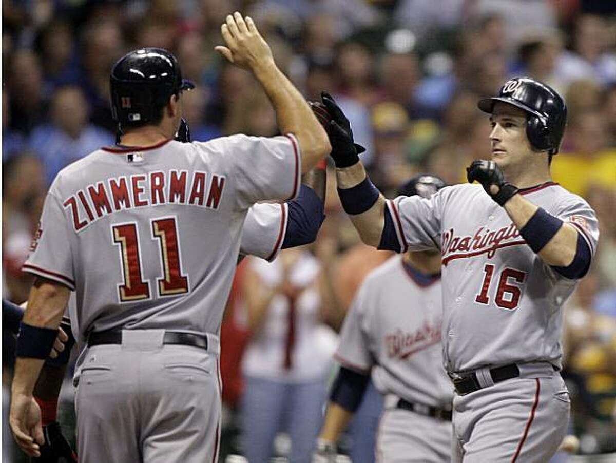 Washington Nationals' Josh Willingham (16) is congratulated at home by Ryan Zimmerman (11) and Cristian Guzman after hitting a grand slam during the fifth inning of a baseball game against the Milwaukee Brewers Monday, July 27, 2009, in Milwaukee. (AP Photo/Morry Gash)