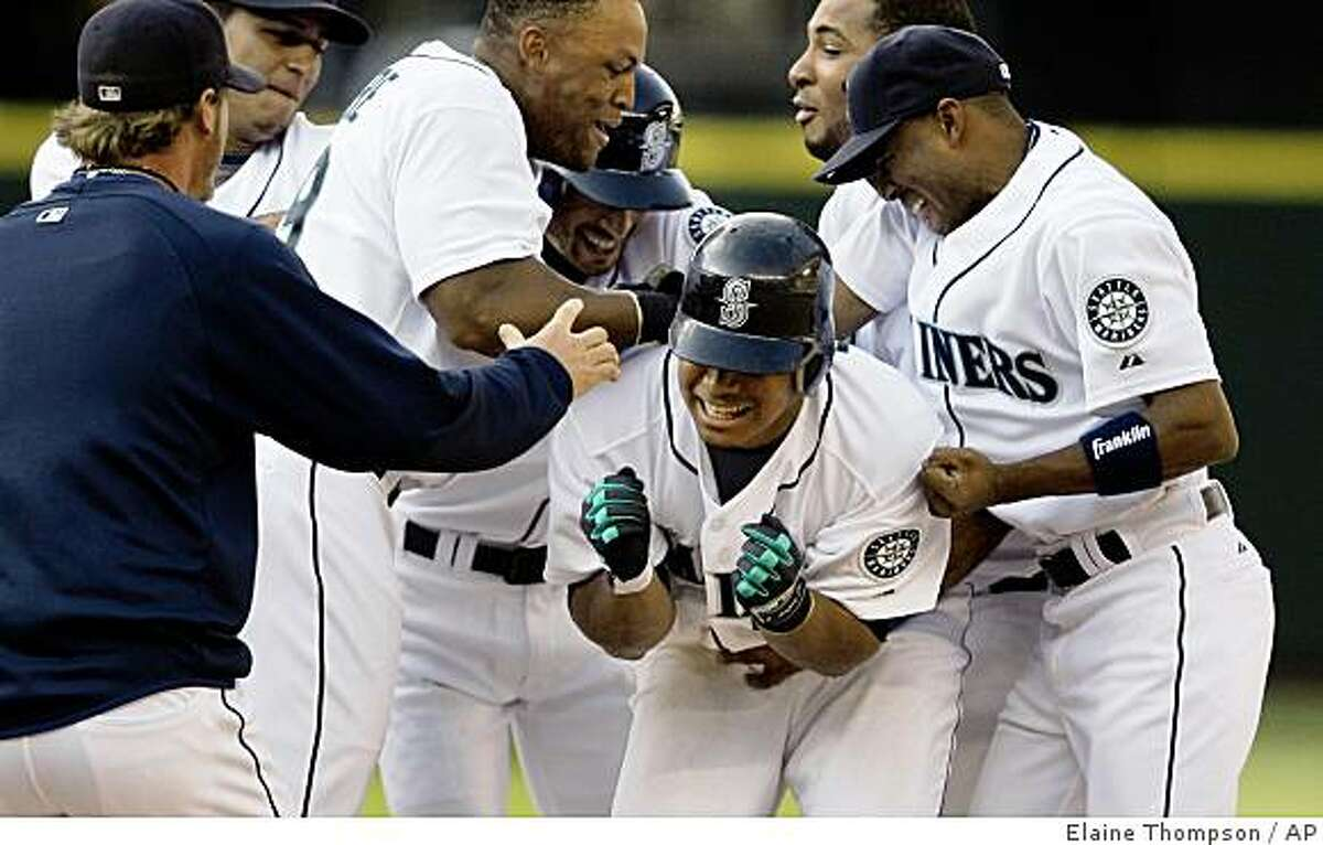 Seattle Mariners' Jose Lopez, center, is greeted by teammates after his bloop single drove in the winning run against the Oakland Athletics in the 15th inning of a baseball game Sunday, May 3, 2009, in Seattle. The Mariners won 8-7. (AP Photo/Elaine Thompson)