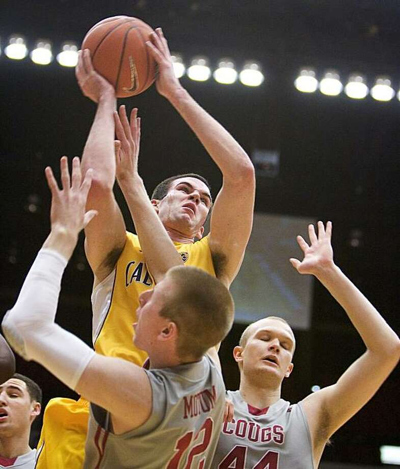 California guard Jeff Powers, top, shoots over Washington State forward Brock Motum (12) as forward Patrick Simon (44) stands in place during the first half of an NCAA college basketball game Saturday, Feb. 12, 2011, in Pullman, Wash. Photo: Dean Hare, AP