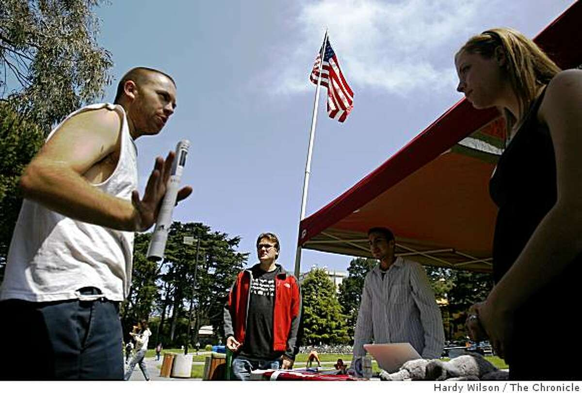 Samuel Lee Harrison, 21, left, of Benicia, speaks to members of the San Francisco State University College Republicans James Kincaid, second from left, Alan Perez, second from right, and Jamie Hunt, right, at the San Francisco State University campus in San Francisco, Calif., on Wednesday, April 22, 2009. The club has been causing controversy on campus with events that many students find offensive.