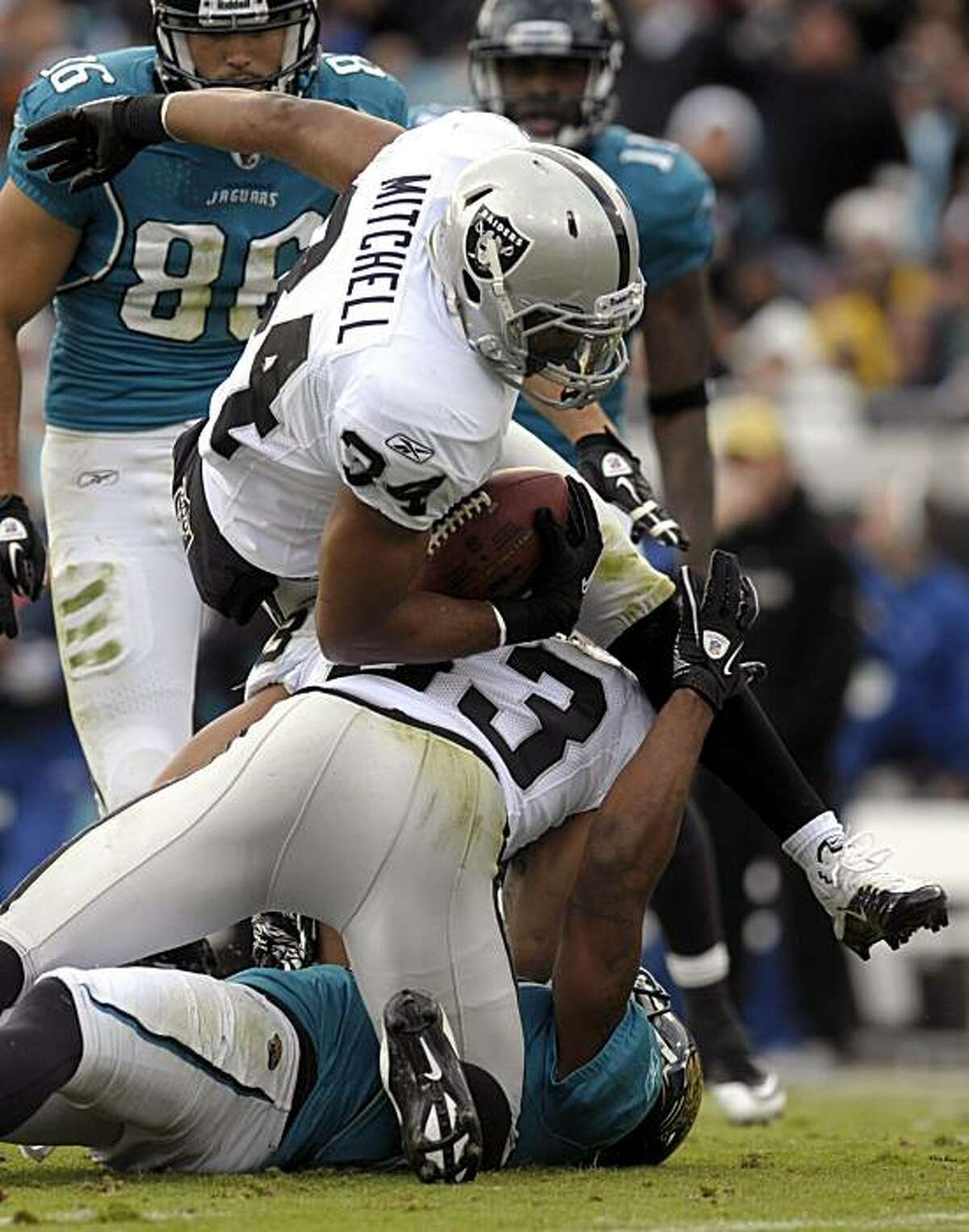 Oakland Raiders safety Mike Mitchell (34) intercepts a pass intended for Jacksonville Jaguars wide receiver Mike Thomas, bottom, after being hit by safety Tyvon Branch (33) during the first half of an NFL football game in Jacksonville, Fla., Sunday, Dec.12, 2010.