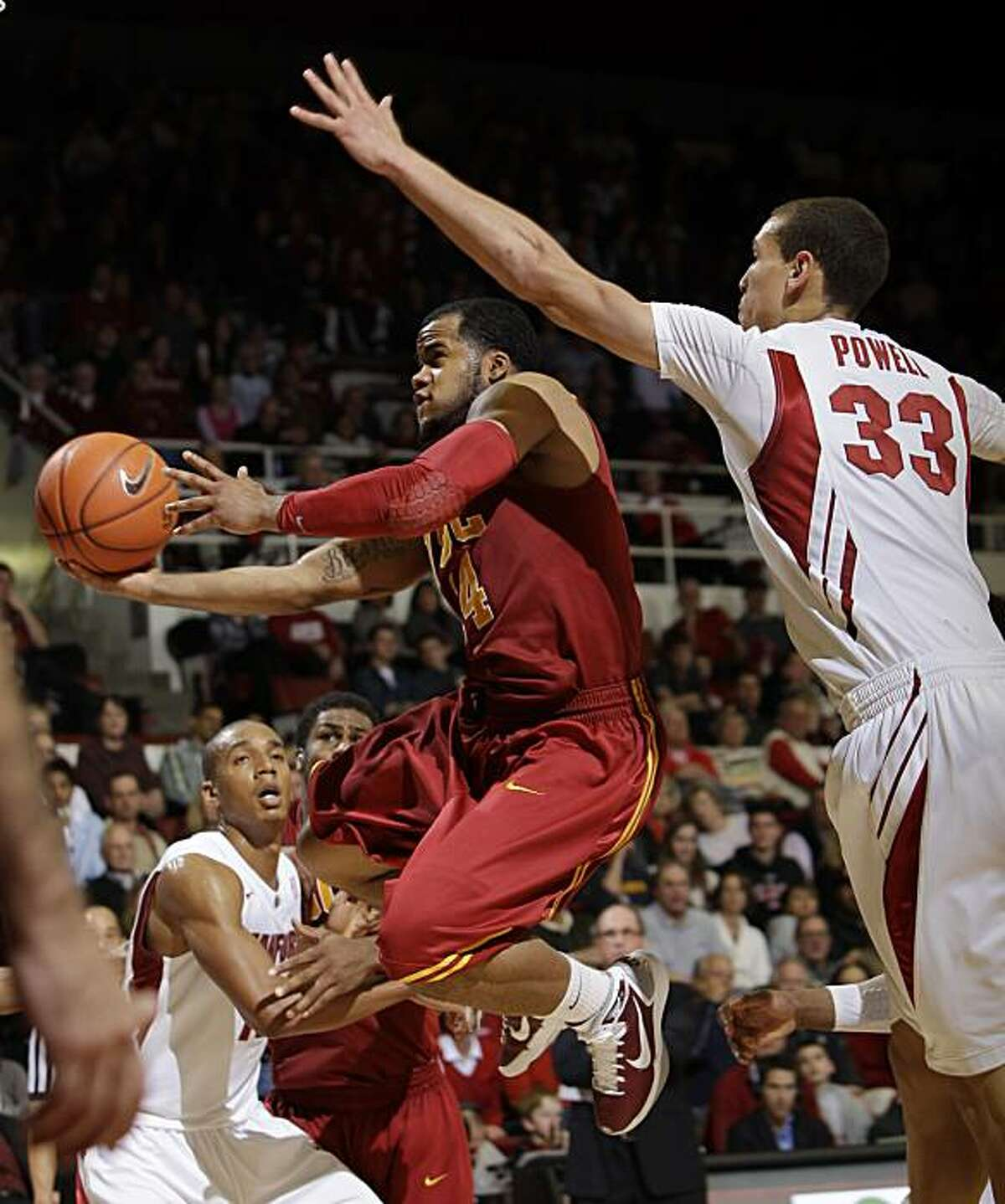 Southern California guard Donte Smith (14) scores in front of Stanford forward Dwight Powell (33) in the second half of an NCAA college basketball game in Stanford, Calif., Saturday, Feb. 19, 2011.