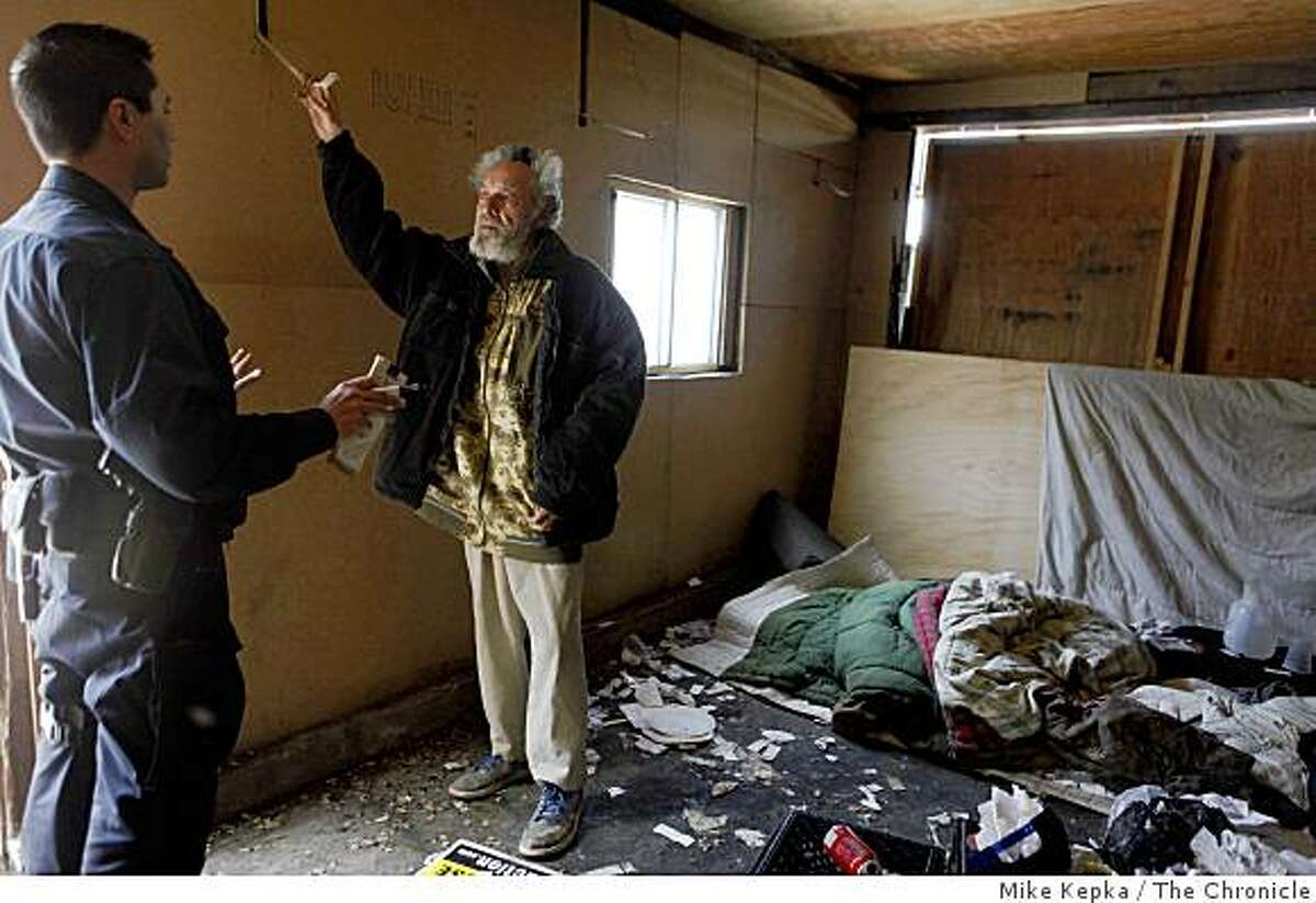 Oakland Problem Solving Police Officer, Mark Castillo warns Alfonso Granera, 71, on Thursday April 30, 2009 in Oakland, Calif. who was found sleeping in the garage of a foreclosed home on 96th Avenue. Castillo said had no current warrants for arrest and that he was going to try to find him a shelter to sleep in.