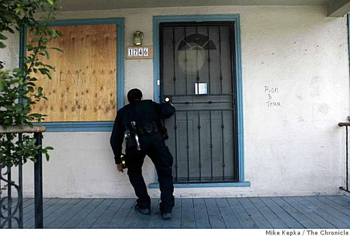 Oakland Problem Solving Police Officer, Mark Castillo, check on the status of a foreclosed home on 96th Avenue on Thursday April 30, 2009 in Oakland, Calif. Later he found a squatter living in the garage.