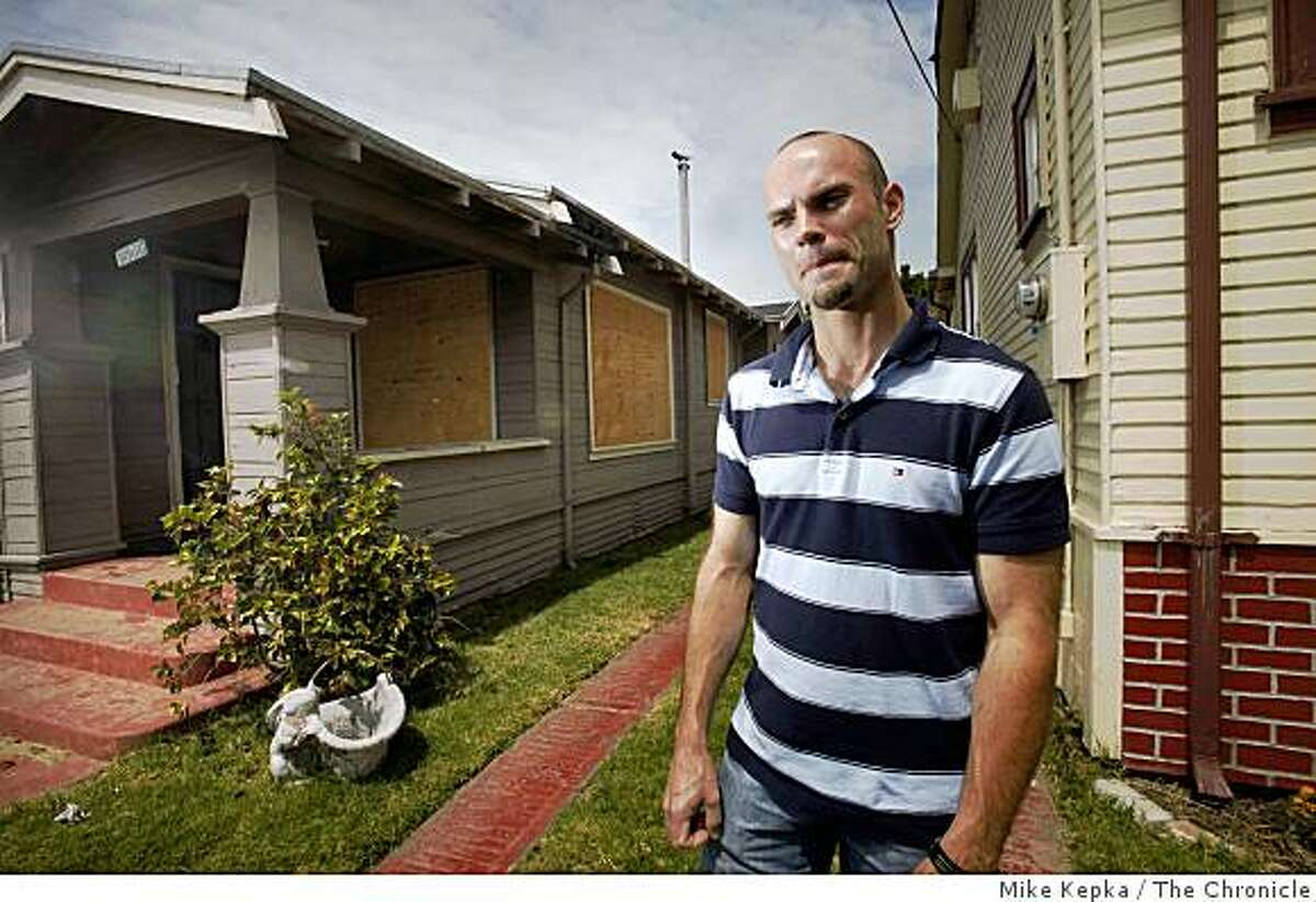 Jeffery Cash stands next to a recently foreclosed house next to his East Oakland home on Thursday April 30, 2009 in Oakland, Calif. Cash feels the boarded up house is greatly adding to a degradation of his neighborhood by adding a new haven for people to do crime, drugs and litter.