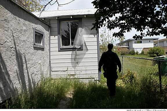 Oakland Problem Solving Police Officer, Mark Castillo, check on the status of a foreclosed home on 94th Avenue on Thursday April 30, 2009 in Oakland, Calif. This property was so bad the first time he encountered his partner got sick because of the smell inside.