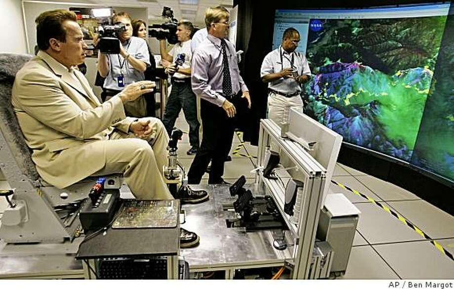 California Gov. Arnold Schwarzenegger, left, gestures as he sits in a flight simulator while viewing aerial infrared images of fire areas in California provided by Steve Hipskind, Chief of the NASA Earth Science Division, at the NASA Ames Research Center in Moffett Field, Calif., Monday, July 14, 2008.  Schwarzenegger and fire officials toured the facility to discuss the important role of NASAs remotely piloted aircraft, named Ikhana, played in Californias wildfire fight. The unmanned aircraft carrying a NASA infrared scanning sensor flew over much of the state this past week, gathering information that was delivered to fire commanders in the field, helping them understand the terrain and behavior of the states most dangerous fires. (AP Photo/Ben Margot) Photo: Ben Margot, AP