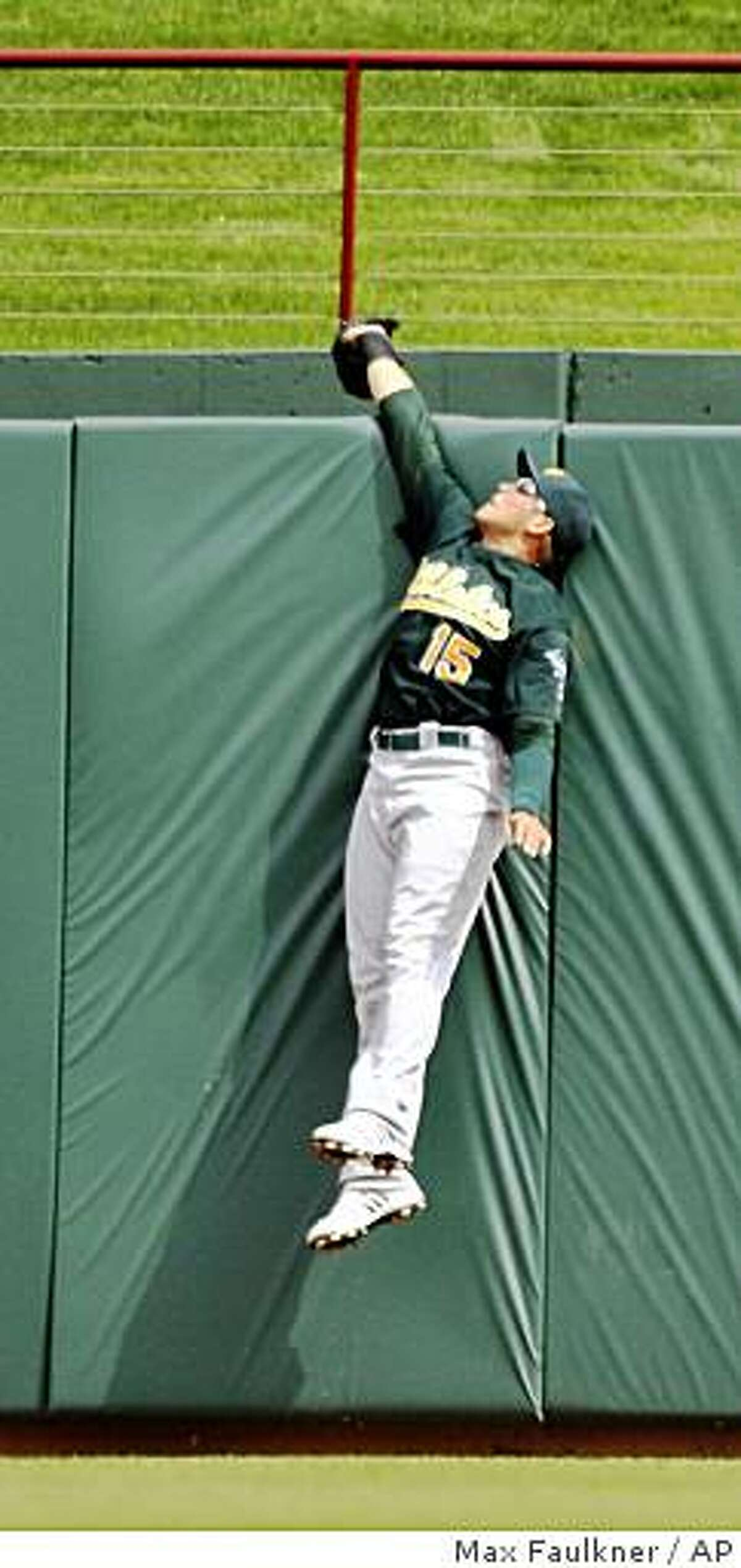 Oakland Athletics' Ryan Sweeney jumps and reaches over the fence to make the catch and rob Texas Rangers' Ian Kinsler of a three-run home run during the eighth inning of a baseball game in Arlington, Thursday, April 29, 2009. The A's won 4-2. (AP Photo/Fort Worth Star-Telegram, Max Faulkner) ** MAGS OUT, NO SALES, ONLINE OUT **