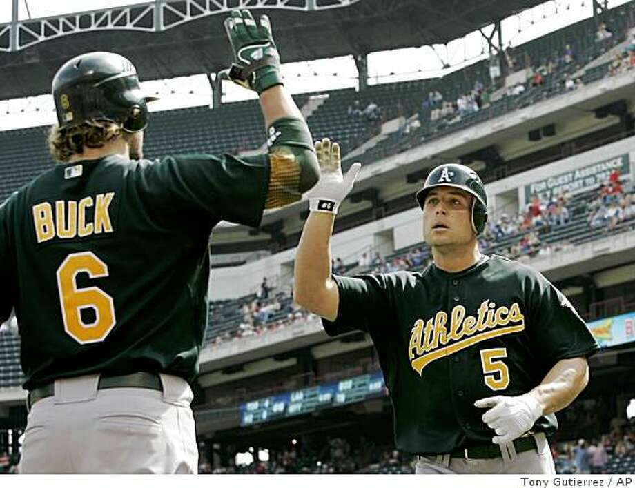 Oakland Athletics' Travis Buck (6) congratulates teammate Matt Holliday (5) on his solo home run off of Texas Rangers' Jason Jennings in the ninth inning of a game in Arlington, Texas, Thursday, April 30, 2009. The Athletics won 4-2. Photo: Tony Gutierrez, AP