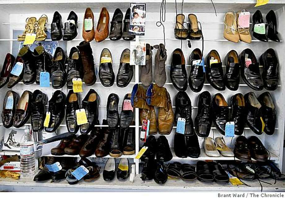 Customers shoes line a wall of the popular shoe repair business, ready to be picked up. Pioneer Renewer Shop is a neighborhood cobbler which has seen a brisk increase in business recently. The shop on 18th Street in San Francisco specializes in the old-school art of shoe repair. Photo: Brant Ward, The Chronicle