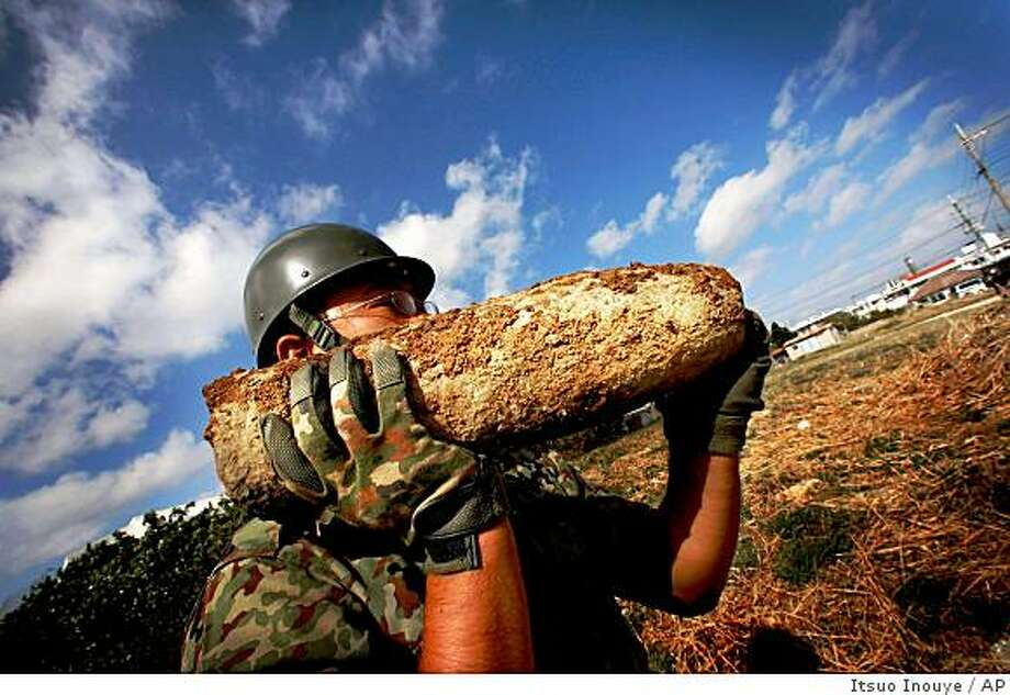 ** ADVANCE FOR SUNDAY, MAY 3 **In this Feb. 13, 2009 photo, a member of the Japan Ground Self Defense Force carries unexploded ordnance in Okinawa, southwestern Japan. Okinawa _ home to more than 1 million people and the site of some of World War II's most savage fighting _ is a tinderbox of unexploded bombs and other ordnance, thousands and thousands of tons of them, rusted and often half buried. (AP Photo/Itsuo Inouye) Photo: Itsuo Inouye, AP