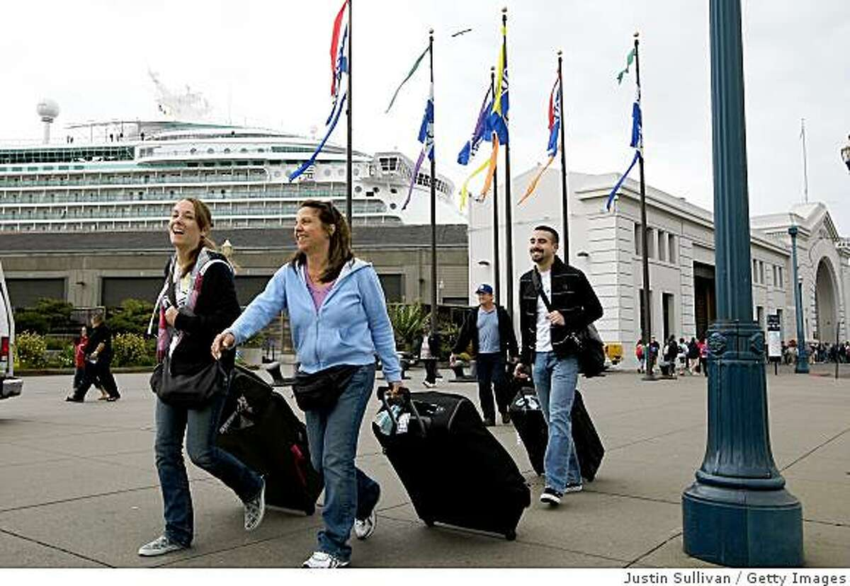SAN FRANCISCO - MAY 01: Passengers from the Royal Caribbean Mariner of the Seas cruise ship pull their luggage after departing from the ship May 1, 2009 in San Francisco, California. Several cruise ships are diverting to the Port of San Francisco instead of heading to destinations in Mexico as health authorities warn against unnecessary travel to Mexico due to the Swine Flu outbreak. (Photo by Justin Sullivan/Getty Images)