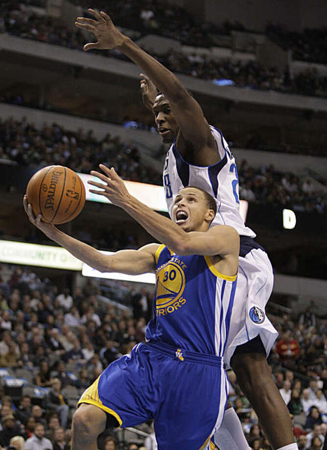 Golden State Warriors guard Stephen Curry shoots the ball as Dallas Mavericks center Ian Mahinmi  (28) looks for the block during the first half of an NBA basketball game in Dallas on Tuesday, Dec. 7, 2010. Photo: Mike Fuentes, AP