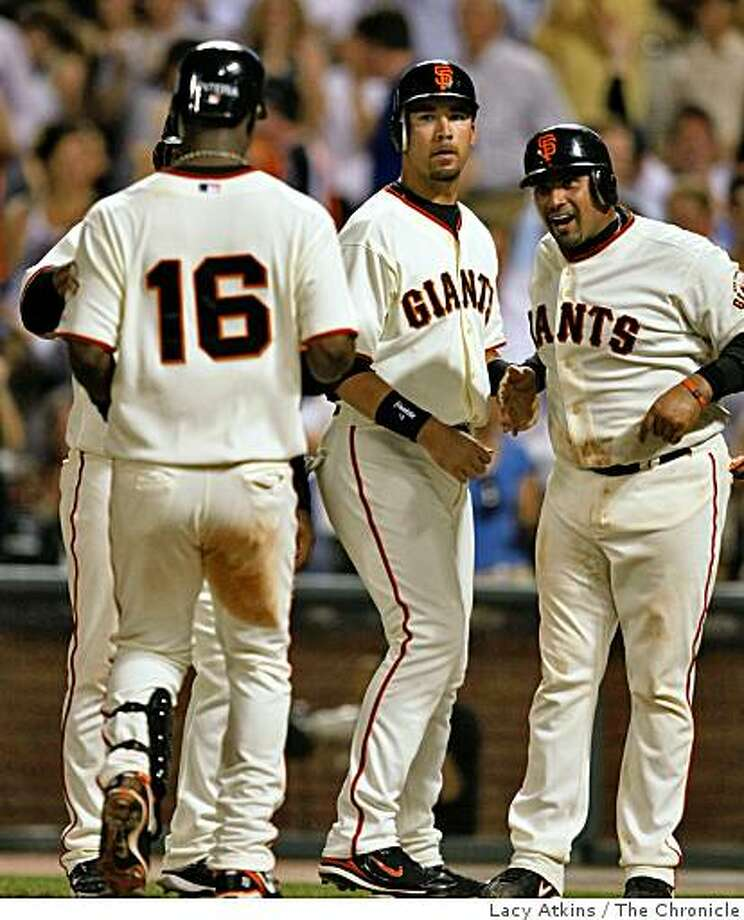 Giants catcher Bengie Molina (right) smiles and congratulates teammate Edgar Renteria as he crosses homeplate after hitting a grandslam against    San Diego Padres, Tuesday April 21, 2009, in San Francisco, Calif. Photo: Lacy Atkins, The Chronicle