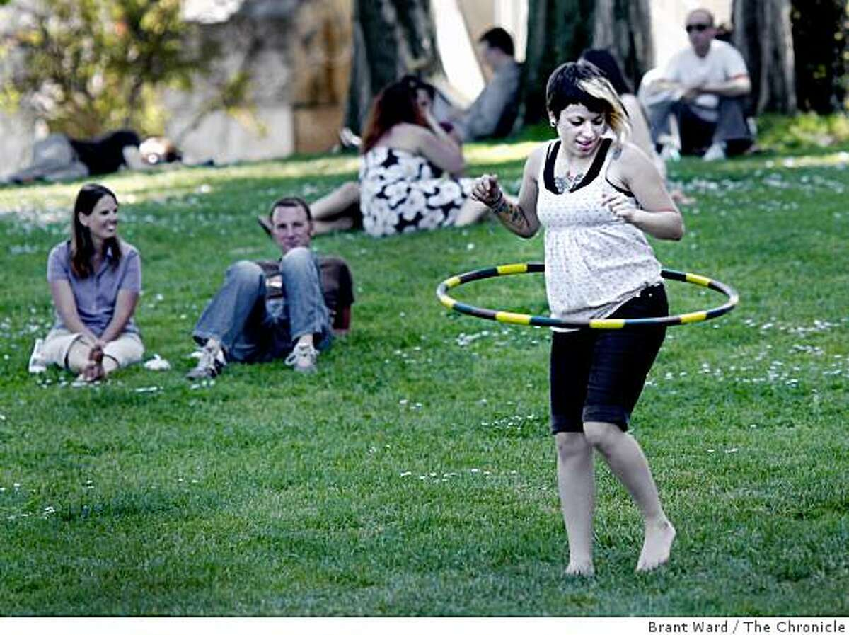 Jeru Weaver from Berkeley practiced her hoop technique on the grass near the Justin Herman Plaza. She has an upcoming hoop performance at Dolores Park she is working on. High daytime temperatures in San Francisco April 20, 2009, caused many locals to find a little shade or perhaps a short nap.