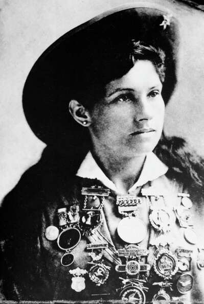 Annie Oakley, American sharpshooter and performer, is shown with a display of medals in this undated