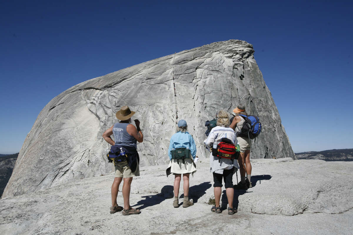 Early in the morning before the crowds arrived, a group of hikers look at the Half Dome cable section in Yosemite National Park on June 30, 2007.