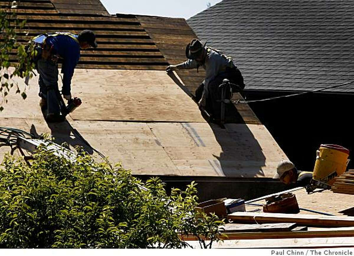 Roofers replace a roof on a home in Berkeley, Calif., on Friday, April 17, 2009.