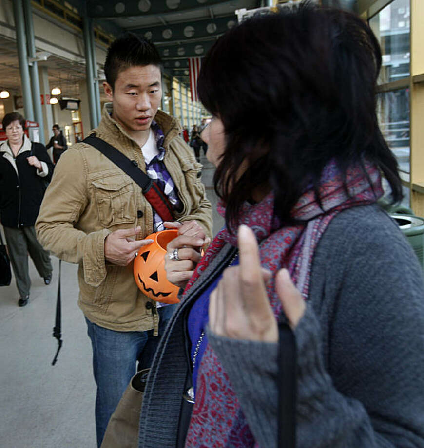 A woman (right) rejects Jason Shen's offer of free candy at the Caltrain Station in San Francisco, Calif., on Thursday, Nov. 4, 2010. Shen is taking part in a practice called Rejection Therapy, which requires participants to be rejected by someone at least once a day to get over their fear of rejection. Photo: Paul Chinn, The Chronicle