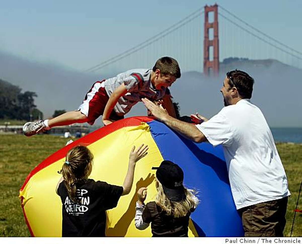 Dylan McAdams, 7, tries to maintain his balance on a bouncing inflatable cube at the Earth Stroll event at Crissy Field in San Francisco, Calif., on Saturday, April 18, 2009. The day-long event was planned as a celebration of Earth Day.