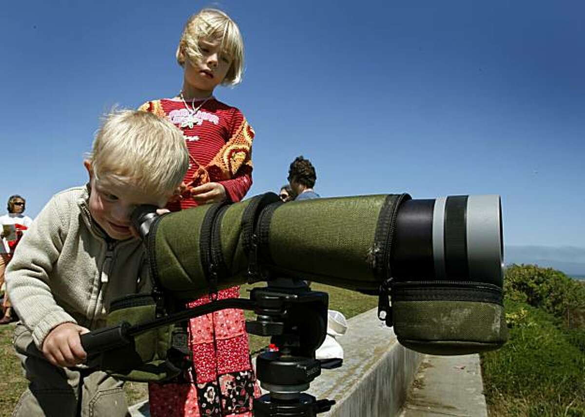 Kai Miglio, 2 1/2, looks at wildlife through a spotting scope while his sister Maia, 6, waits her turn during the Earth Stroll event at Crissy Field in San Francisco, Calif., on Saturday, April 18, 2009. The day-long event was planned as a celebration of Earth Day.