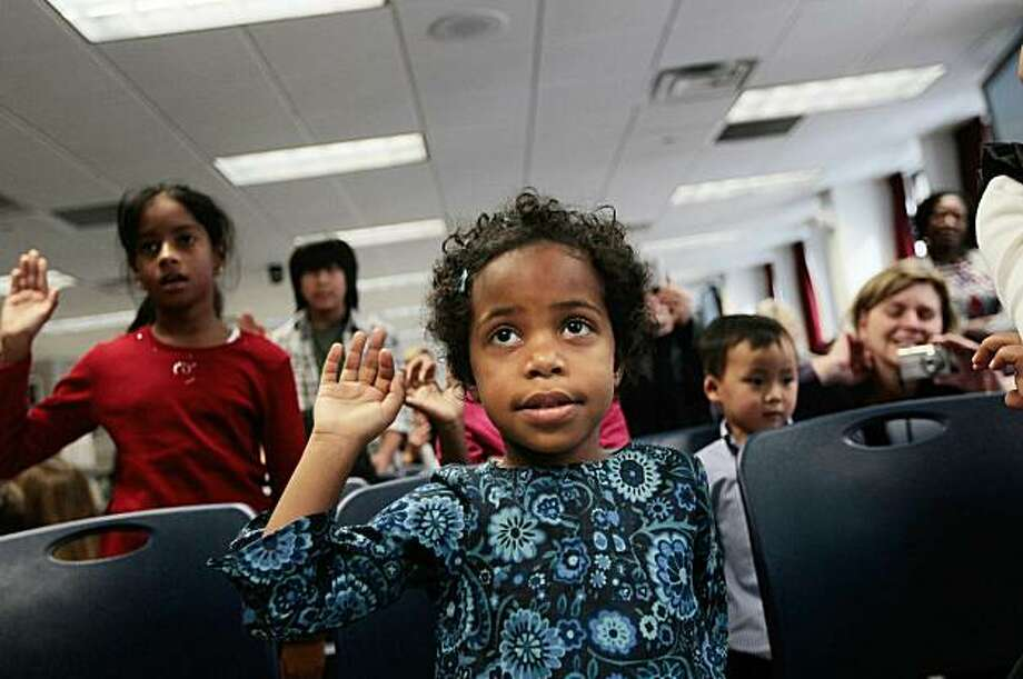 NEW YORK - NOVEMBER 18:  Mirette Franklin, 4, originally from Ethiopia, recites the Oath of Allegiance to get her American citizenship with other chiildren November 18, 2010 at the US Citizenship and Immigration Services offices in New York. Eighteen children, originally from Haiti, Ethiopia, China, and other countries, were sworn in as citizens with their American adopted parents standing by in a ceremony at the New York headquarters from USCIS.  (Photo by Chris Hondros/Getty Images) *** BESTPIX *** Photo: Chris Hondros, Getty Images