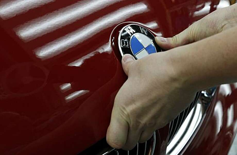 A Bayerische Motoren Werke AG places a badge on a BMW vehicle on the assembly line at the company's auto plant in Leipzig, Germany, on Friday, Nov. 5, 2010. Bayerische Motoren Werke AG, the world's largest maker of luxury vehicles, said it will invest 530 million euros ($751 million) to set up production of its Megacity electric-powered city car. Photographer: Michele Tantussi/Bloomberg Photo: Michele Tantussi, Bloomberg