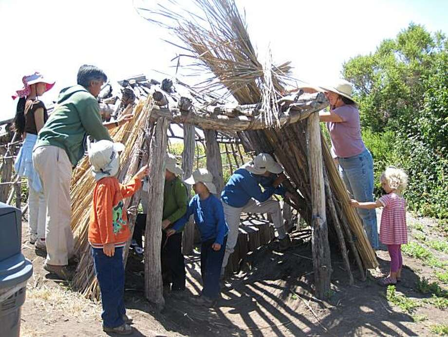 Students from the Fremont Unified School District Native American Studies Program inside an Ohlone-style cattail house Photo: Beverly Ortiz